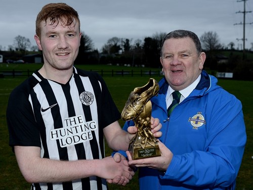 Ciaran Reid receives his man of the match trophy from Enda Love of the IFA Junior Committee.jpg