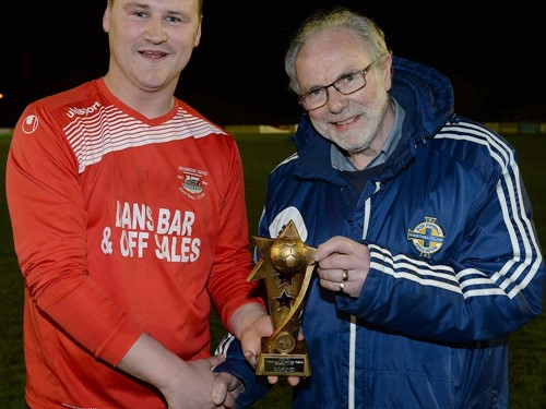 Man of Match Declan Monaghan of Bessbrook United recieves his trophy from Brian Larkin of the Irish FA Junior Committee.jpg