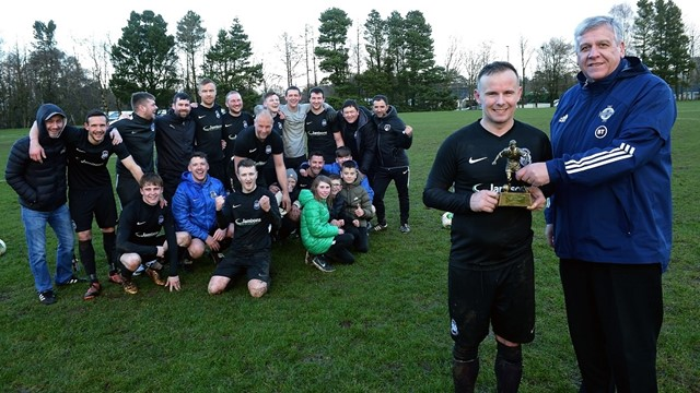 __Man of the Match__Bryan Tosh of Dervock receives his trophy from Wayne Glynn, Vice-Chairman of the Irish FA Junior Committee, as his team mates look on.jpg
